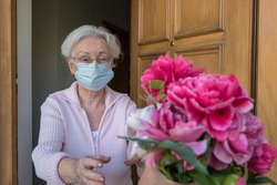 Senior woman with protective mask gets flowers on mothers day
