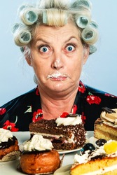 Senior Woman with Rollers in her Hair, indulging in her Guilty pleasure of eating too many cakes / Sweets: What? Who, me?!