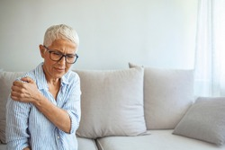 Senior woman with shoulder pain. Elderly woman is enduring awful ache. Neck and shoulder pain, old woman suffering from neck and shoulder injury, health problem concept