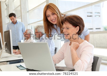 Senior woman with trainer in front of laptop computer