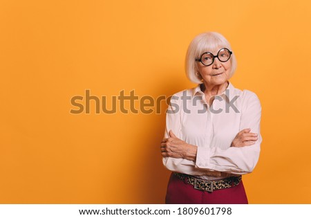 Senior woman with white hair in round glasses wearing white blouse, red pants and leopard print belt, crossing her hands and looking at camera. Woman isolated over orange background