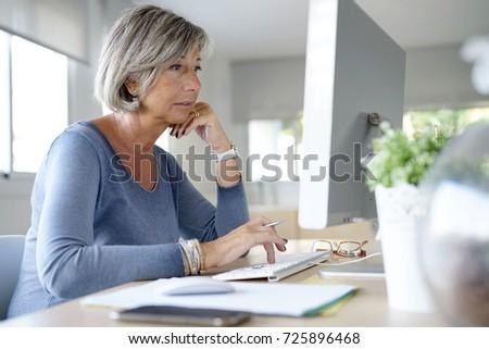 Senior woman working in office on desktop computer