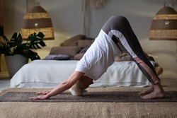 Senior woman working out at home, doing yoga exercise in the room downward facing dog pose, adho mukha svanasana fron sun salutation pose.