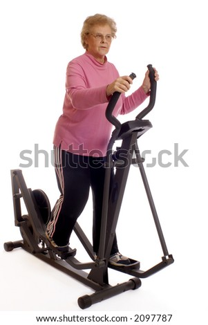 "Senior woman working out on no-impact elliptical ""walking machine""  Isolated on white."