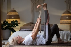 Senior woman working out, warming up using yogic belt, lying in yoga Supta Padangushthasana, One Leg Lift exercise, reclined variation of Extended Hand to Big Toe pose at home.