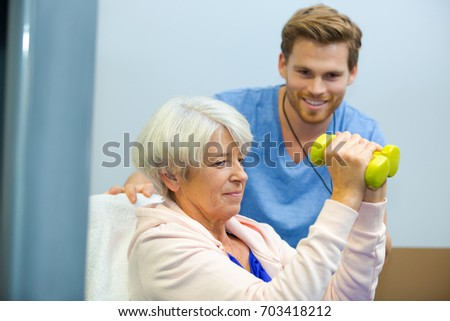 senior woman working out with dumbbells with personal trainer