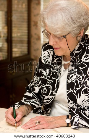 Senior woman writing personal letter to a friend in her home.