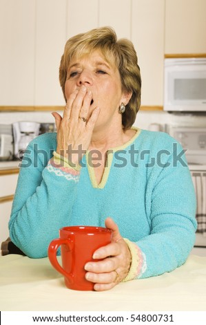 Senior woman yawns while sitting at her kitchen table with a coffee mug