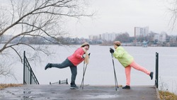 Senior women in autumn park doing warm up before nordic walking
