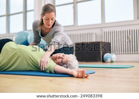 Senior women lying on exercise mat doing stretching workout for back muscles with coach assistance. Female trainer helping elder woman in stretching.