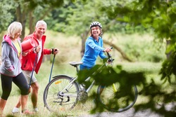 Seniors exercise fitness in nature with mountain bikes and hiking poles