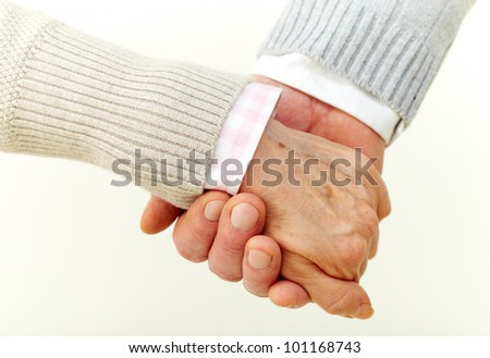 Seniors holding hands indicating their commitment to each other