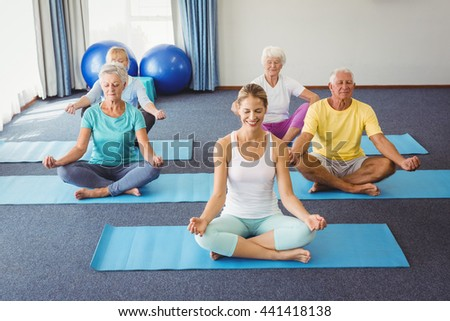 Seniors relaxing in lotus position during fitness class