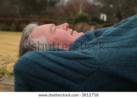 Seniors retired man lying on back sleeping in park