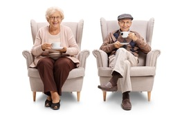 Seniors seated in armchairs drinking tea and looking at the camera isolated on white background