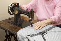Seniors sew clothes on an old sewing machine. An old white hair woman sews on an old sewing machine. Tailoring of an old seamstress woman