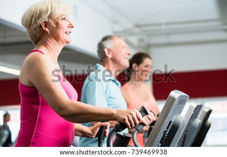 Seniors training on cross trainer with personal trainer at the gym