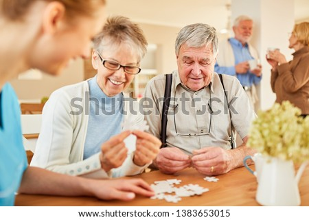 Seniors with Alzheimer's disease or dementia playing puzzle with senior care #1383653015