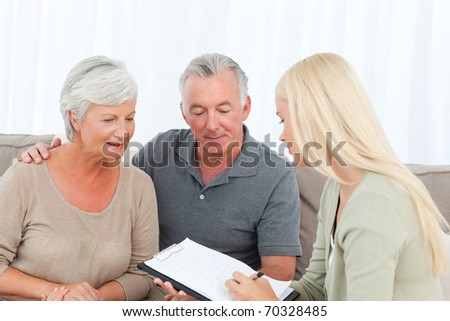 Seniors with doctor at home - stock photo