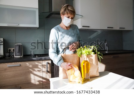 Seniors woman  wearing medical face mask Disassembles food bags at home in the kitchen. quarantine. health concept. Corona Virus. order of products online. Delivering products to home