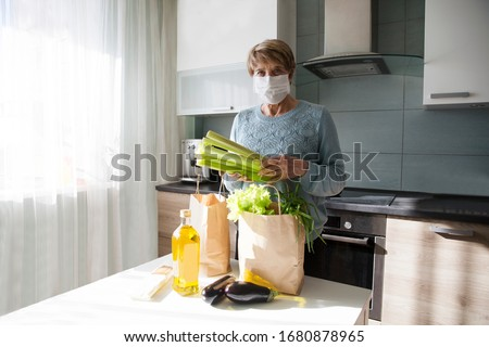 Seniors woman  wearing medical face mask with food bags at home in the kitchen. quarantine. health concept. Corona Virus. order of products online. Delivering products to home