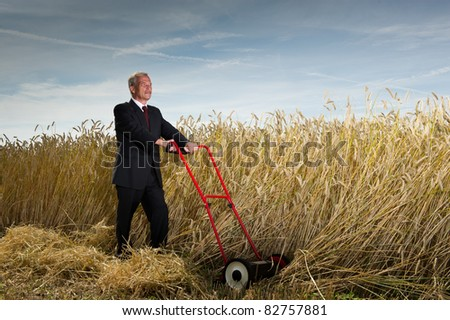 Seniot executive businessman pausing during the challenge of harvesting a field of ripe wheat with a hand lawnmower as he visualises the rewards to be gained at the completion of his task