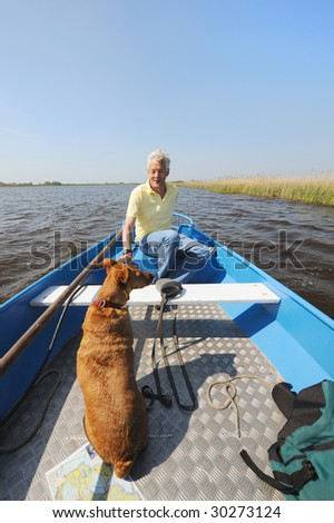 Senoir man is with boat and dog in nature