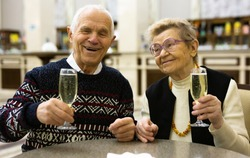 Senor and senora communicating and drinking champagne in hall of cafeteria