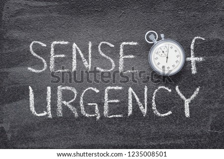 sense of urgency phrase handwritten on chalkboard with vintage precise stopwatch used instead of O