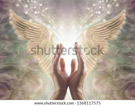 Sensing Angelic Energy - Male hands reaching up into a beautiful pair of golden Angel wings with white light and sparkles flowing  between, against a warm ethereal energy formation background