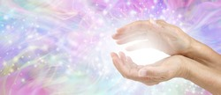 Sensing Awesome Metaphysical Energy Field between hands - female cupped hands with white healing energy against a colourful blue purple green sparkling chaotic background with copy space