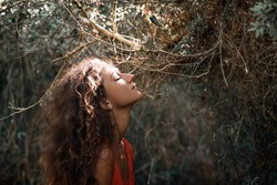 sensitive portrait of beautiful young woman in forest
