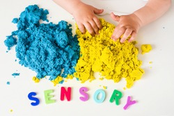 Sensory word, magic kinetic sand and kids hands close up. Early sensory education. Kids's sensory experiences,  games for fine motor skills. Therapy hand, development of fine motor, autism