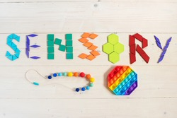 Sensory word written of colored wooden geometric shapes. Sensory integration therapy. Activities Montessori, games for sensory processing disorder, child development and occupational therapy