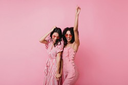 Sensual african lady having fun with her best friend. Indoor photo of adorable girls in pink clothes standing on light background.