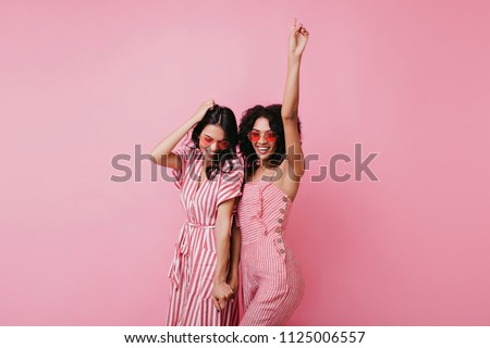 Sensual african lady having fun with her best friend. Indoor photo of adorable girls in pink clothes standing on light background. #1125006557