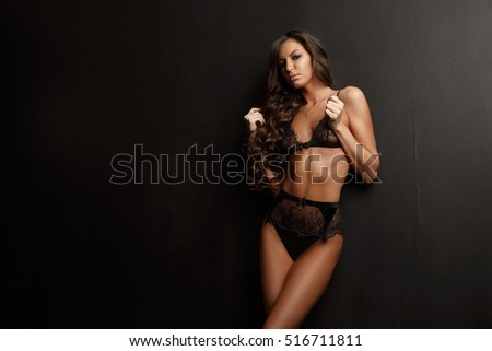 Sensual and appealing young woman with dark wavy hair, long legs and bronzed skin is posing in the black lacy translucent underwear in the studio  room near the wall, dark background  #516711811