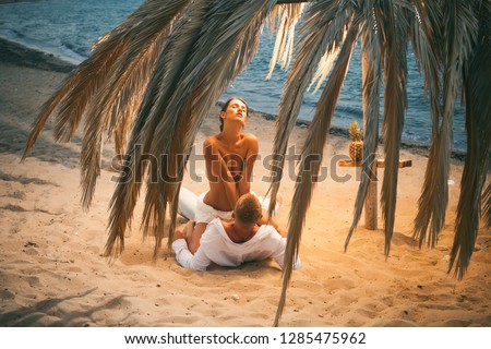 Sensual. Attractive couple having sex on the beach. Sex on beach concept. Couple full of desire have sex on sand of seashore. Sensual lovers making love at seashore, sea on background. Vacation.