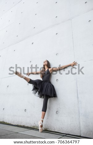 Sensual ballerina with closed eyes stands on the left toe and leans on the textured concrete wall outdoors. Her right leg and arms are outstretched to the sides. Girl wears a dance wear and pointes. #706364797