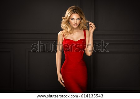 Sensual beautiful blonde woman posing in red dress. Girl with long curly hair. #614135543