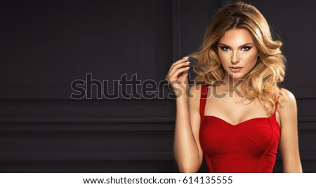 Stock Photo Sensual beautiful blonde woman posing in red dress. Girl with long curly hair.