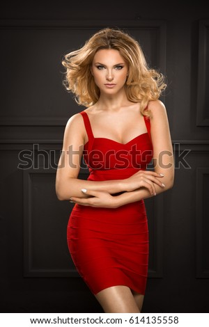 Sensual beautiful blonde woman posing in red dress. Girl with long curly hair. #614135558