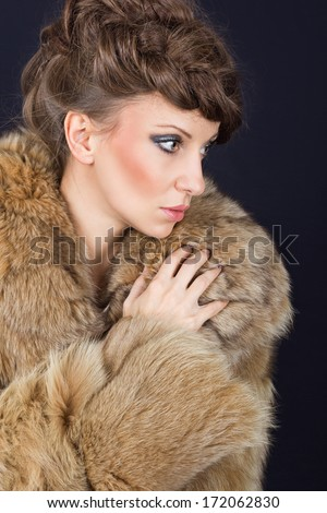 Sensual beautiful brunette Caucasian woman wearing brown fur coat looking sideways posing against black background. Fashion portrait.
