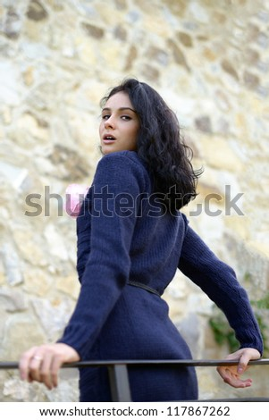 Sensual beautiful girl with rose staying on the bridge of old castle near rough stone wall. Tuscan, Italy