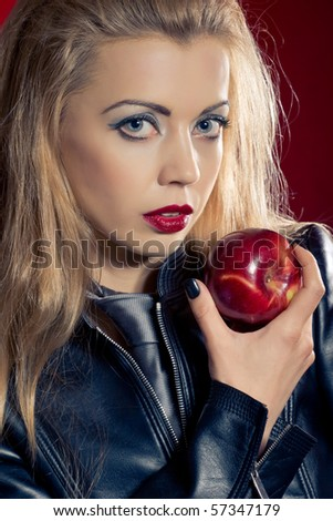 Sensual blond girl wearing a leather jacket offering an apple