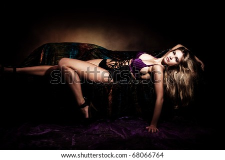 sensual blond woman in lingerie lie on bed, studio shot, dark background