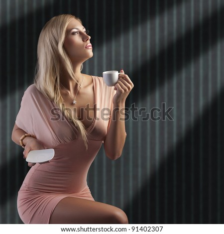 sensual blond woman with hair style holding a cup of coffee in elegant pink dress over dark fashion background