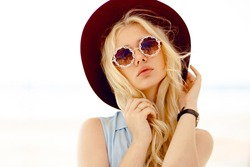 Sensual blonde girl with round floral eyeglasses,curly hair,big lips and burgundy hat touches own hair and looking aside.Horizontal view.
