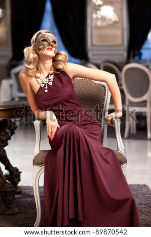 Sensual blonde with a mask, sitting in a ballroom. Please see more images from the same shoot.
