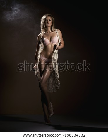Sensual blonde woman posing in black sensual lingerie with toothy smile, looking at camera. Studio shot